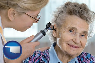 a otolaryngologist examining the ear of a patient - with Oklahoma icon