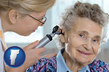 a otolaryngologist examining the ear of a patient - with Vermont icon