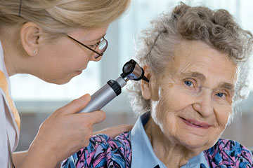 a otolaryngologist examining the ear of a patient